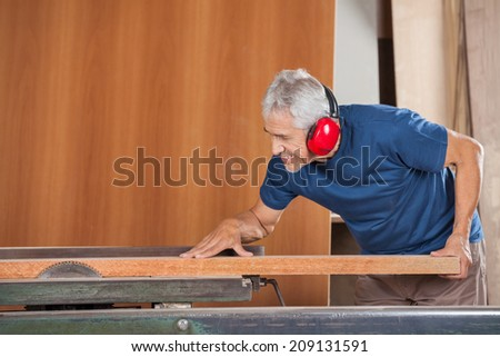 Senior male carpenter cutting wooden plank with tablesaw in workshop - stock photo