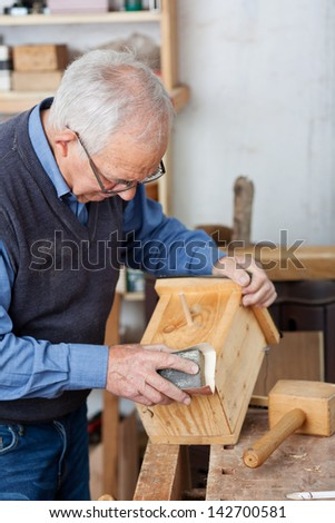 Senior male carpenter using sandpaper for polishing birdhouse at worktable in workshop - stock photo