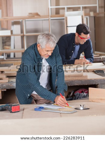 Senior male carpenter working on blueprint with colleague in background at workshop - stock photo