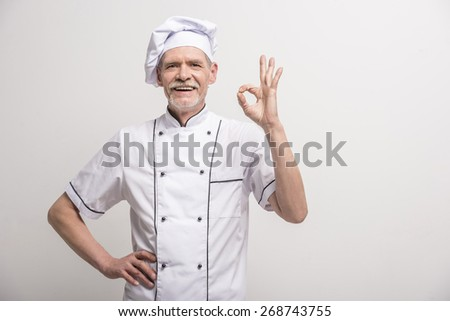 Senior male chief cook in uniform gesturing okay sign on grey background. - stock photo