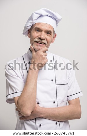 Senior male chief cook in uniform on grey background. - stock photo