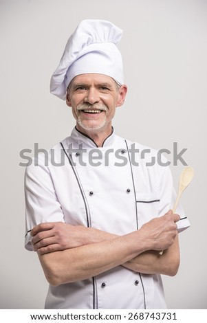 Senior male chief cook in uniform with crossed hands  with wooden snoop a  on grey background. - stock photo