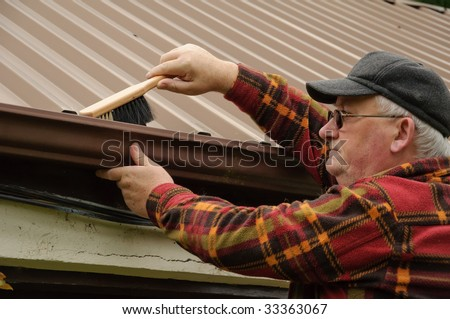 senior male cleaning out the shed gutter with brush. winter repair maintenance service