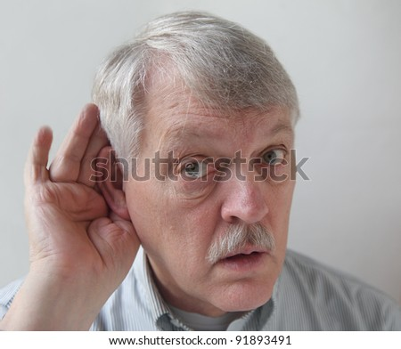 senior male cups his ear in order to hear better - stock photo