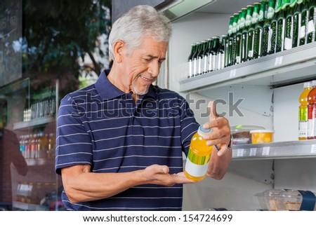 Senior male customer reading information on juice bottle at supermarket - stock photo