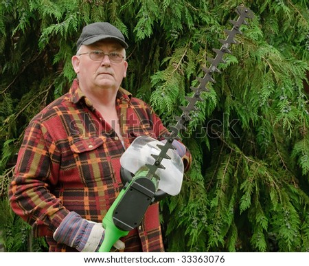 senior male cutting back tree branches in garden - stock photo