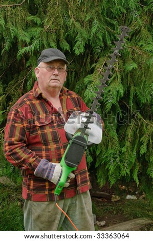 senior male cutting back tree branches in garden with chainsaw - stock photo