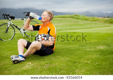 senior male cyclist taking a break and drinking water outdoors