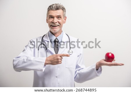 Senior male doctor holding red apple on grey background. - stock photo