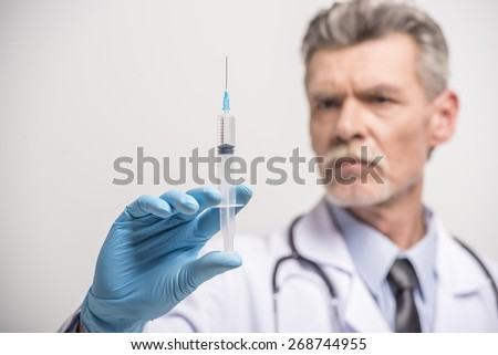 Senior male doctor in gloves with syringe on grey background. - stock photo
