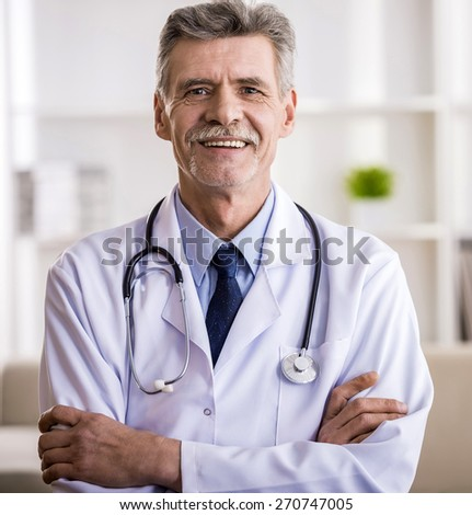 Senior male doctor is looking at the camera and smiling. - stock photo
