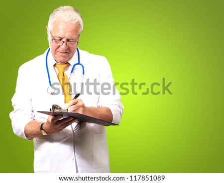 Senior Male Doctor Writing On Clipboard Isolated On Green Background - stock photo