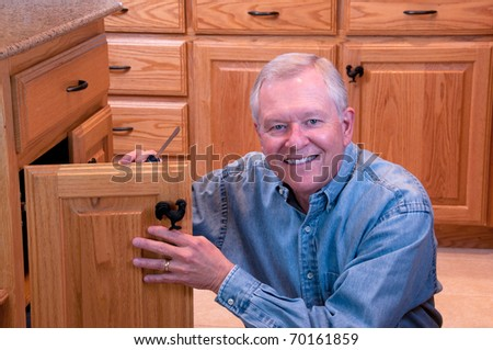 Senior male doing home repair - cabinet knob replacement - stock photo
