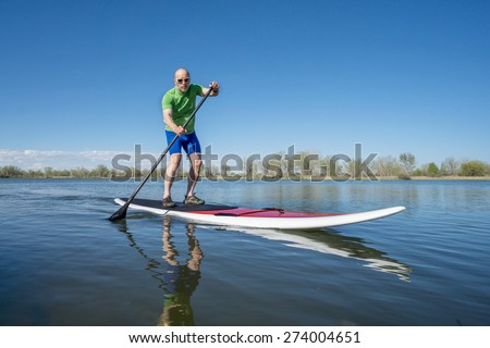 Senior male exercising on stand up paddling (SUP) board. Early spring on a calm lake in Fort Collins, Colorado.. - stock photo