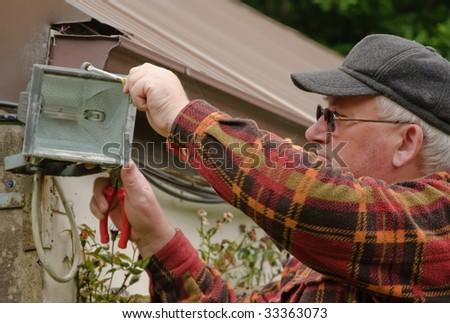 senior male fixing outside light in garden - stock photo