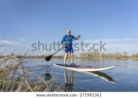 Senior male on stand up paddling (SUP) board. Early spring on calm lake in Colorado. - stock photo