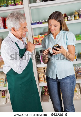 Senior male owner assisting female customer in choosing product in grocery store - stock photo