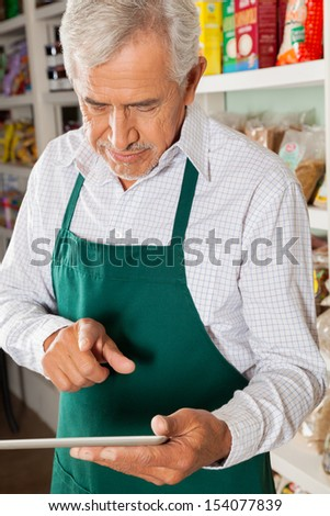 Senior male owner using digital tablet in grocery store - stock photo