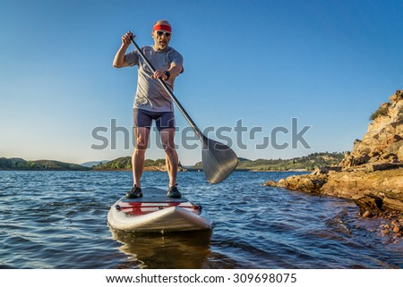 senior male paddler enjoying stand up paddling on a sunny summer day - Horsetooth Reservoir, Fort Collins, Colorado - stock photo