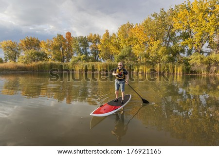 senior male paddler enjoying workout on stand up paddleboard (SUP), calm lake in Colorado, fall colors - stock photo
