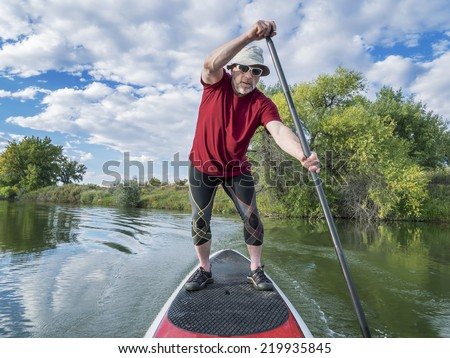 senior male paddler enjoying workout on stand up paddleboard (SUP), calm lake in Colorado, late summer - stock photo