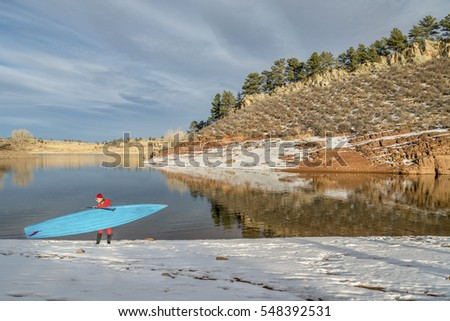 senior male paddler in drysuit and stand up paddleboard on lake in Colorado, winter scenery