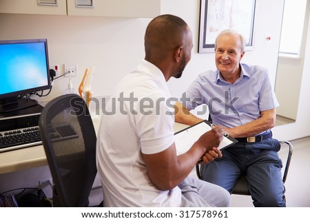 Senior Male Patient Working With Physiotherapist In Hospital - stock photo