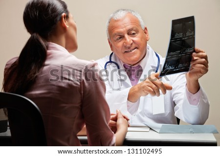 Senior male radiologist explaining x-ray to female patient - stock photo