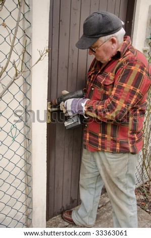 senior male repairing a wooden door latch with drill - stock photo