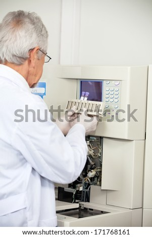 Senior male scientist loading analyzer with samples in medical laboratory - stock photo