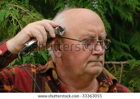 senior male shaving and cutting his hair - stock photo