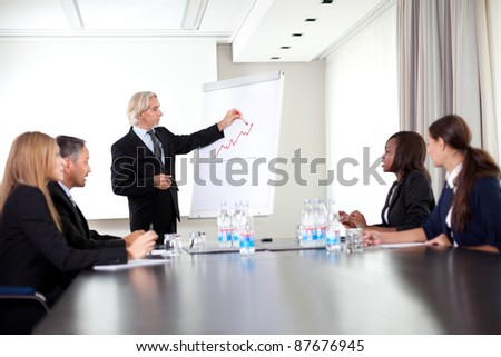 Senior male speaker giving presentation at a business meeting - stock photo