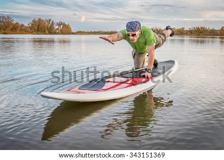 senior male stretching and warming up on a paddleboard before paddling workout on a lake in Colorado - stock photo