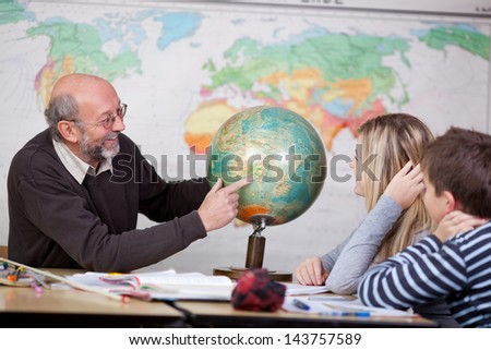 Senior male teacher pointing at globe while students looking at it at desk in classroom - stock photo