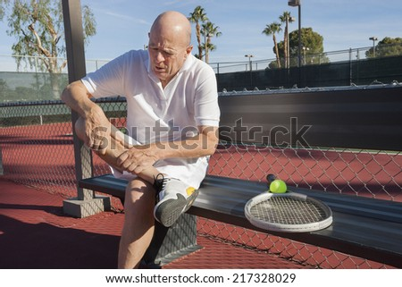 Senior male tennis player with leg pain sitting on bench at court - stock photo