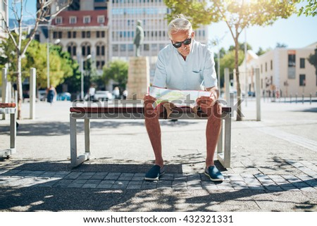 Senior male tourist sitting on a bench and looking for a place on the map. Mature man sitting outdoors in the city and reading a map on a summer day. - stock photo