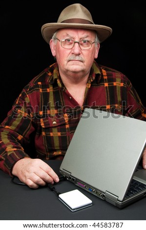 senior male with laptop and external hard drive on black