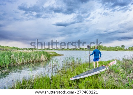 senior male with stand up paddleboard on lake shore watching stormy clouds - stock photo