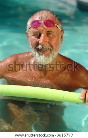 Senior man, a former professional swimmer, working out in the pool on a hot summer day - stock photo