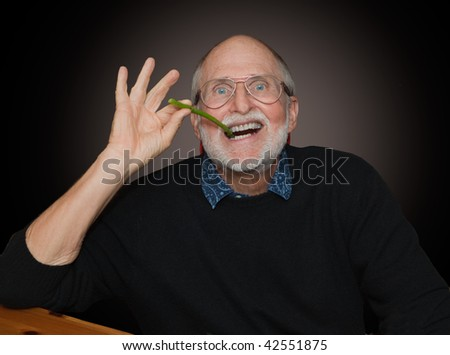 Senior man acts like Groucho Marx smoking an asparagus - stock photo