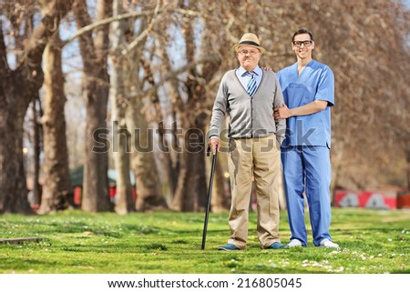 Senior man and a male nurse posing in park on a sunny day - stock photo