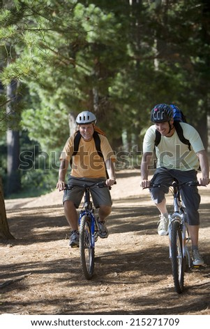 Senior man and adult son, with cycling helmets and rucksacks, mountain biking along woodland trail, smiling, front view - stock photo