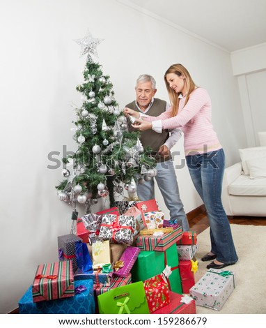 Senior man and daughter decorating Christmas tree together at home - stock photo