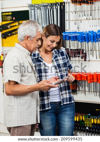 Senior man and daughter looking at wrench while standing in hardware shop - stock photo