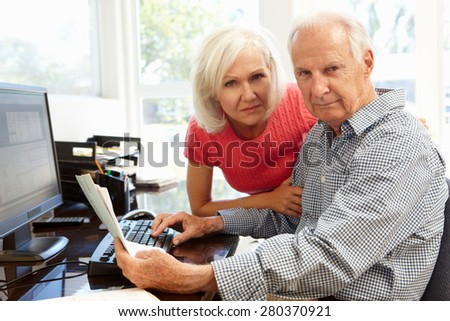 Senior man and daughter using computer at home - stock photo