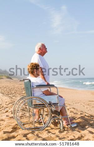senior man and disable wife on beach - stock photo