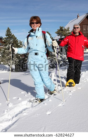 Senior man and senior woman smiling in snow with snow-shoes