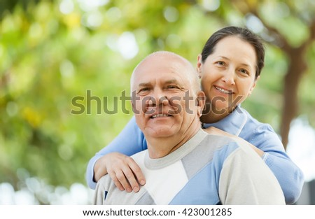 senior man and smiling mature woman together against blured trees