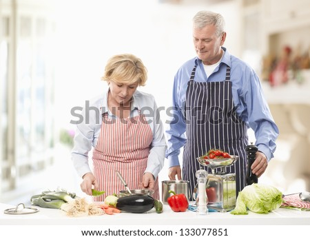 Senior man and woman cooking together in the kitchen. - stock photo