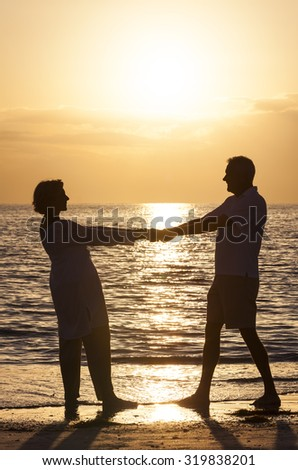 Senior man and woman couple holding hands at sunset or sunrise on a deserted tropical beach